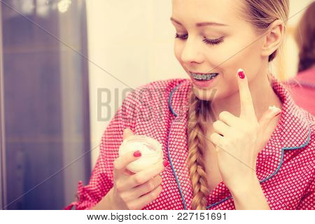 Young Blonde Woman In Bathroom Applying Moisturizing Skin Cream On Face. Girl Taking Care Of Dry Com