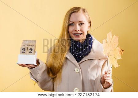 Woman Holding Calendar With First Autumn Day 22 September And Big Leaf. Studio Shot On Yellow Backgr