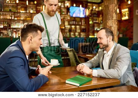 Informal Meeting Of White Collar Workers: They Sitting At Cafe Table And Discussing Joint Project Wh