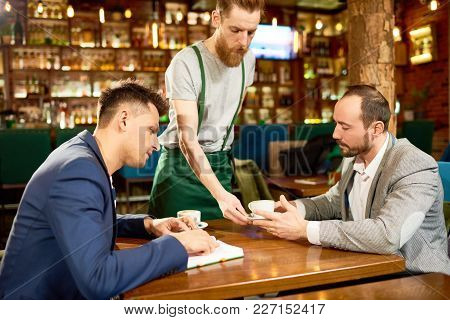 Two Handsome Colleagues Wearing Stylish Suits Sitting At Cafe Table And Brainstorming On Start-up Pr
