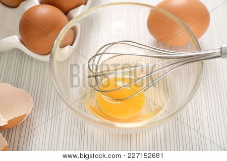 Beating up chicken eggs with whisk in glass bowl on table