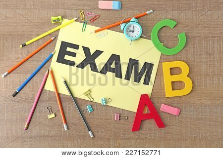 Paper with word EXAM and stationery on wooden background
