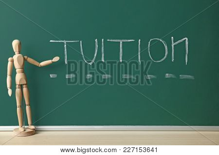 Word TUITION written on chalkboard