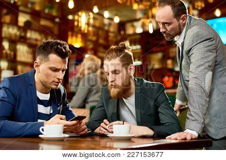 Handsome Young Manager Using Smartphone While Having Informal Working Meeting With Colleagues, Inter