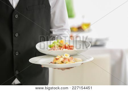Waiter holding plates with dishes at banquet, closeup