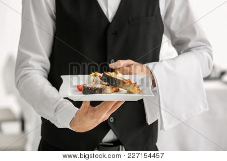 Waiter holding plate with fish and rice, closeup