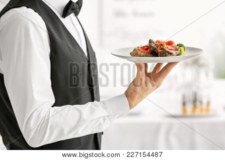 Waiter holding plate with meat and vegetables, closeup