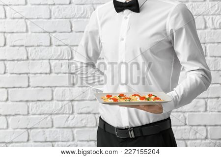 Waiter holding plate with appetizer on brick wall background