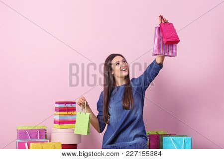 Happy woman with shopping bags against color background