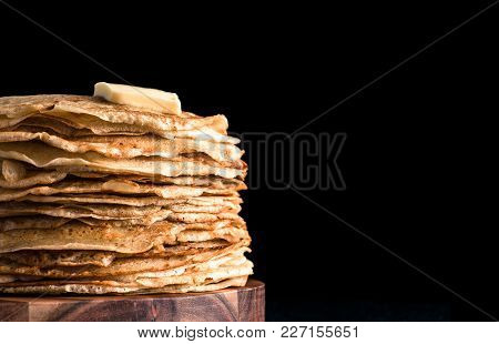Stack Of Traditional Russian Pancakes Blini Isolated On Black Background With Copy Space. Homemade R