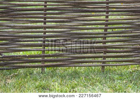Fence Of Wooden Twigs On Green Grass. Natural Tree Trunk Texture. Garden Decor, Barrier, Border, Bou
