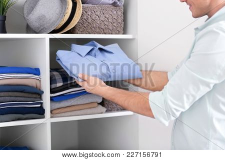 Man picking outfit from closet. Fashionable wardrobe