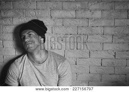 Homeless poor man near brick wall