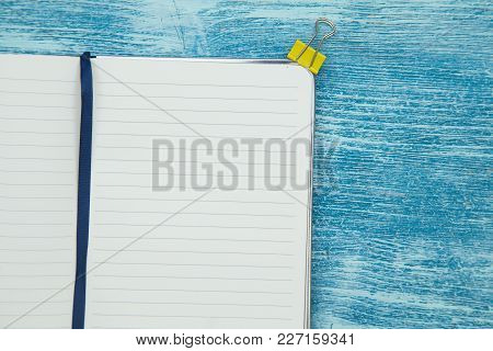 Education Concept. Opened Blank Notepad And Yellow Paper Clip On A Blue Wooden Background, Top View,