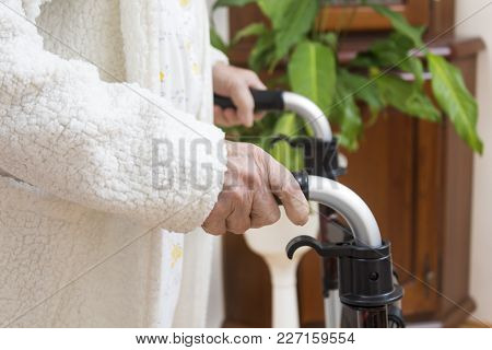 Grandma In A White Bathrobe. The Wrinkled Hands Of A Very Old Woman Hold The Handles Of The Walker H