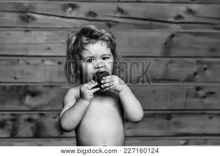 Small Boy Child With Long Blonde Hair Eating Red Nectarine Or Peach Fruit With Bare Chest And Cute F