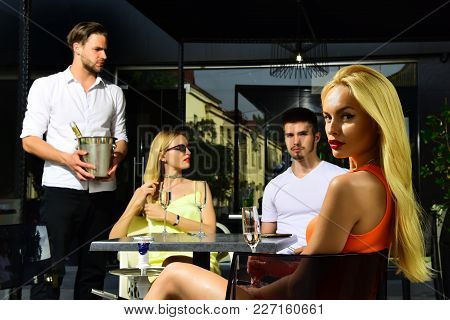 Friends Drink Champagne In Cafe Outdoor. Men And Sensual Twin Women In Bar On Summer Day. Addiction,