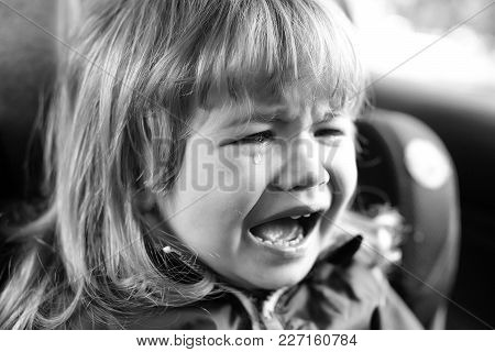 Small Boy Child With Facial Emotions On Unhappy Crying Face And Long Blonde Hair Sitting In Car With