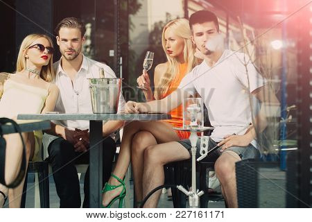 Addiction, Bad Habits. Twins Women And Men Relax In Shisha Cafe Outdoor. Friends Vapor Hookah And Dr