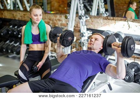 Couple At The Gym. A Personal Trainer Explains To A Young Woman Exercises With A Dumbbell. Man And W