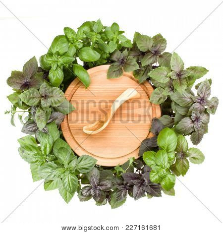 Round wooden cutting board with spoon. Various sweet basil herb leaves edged.. Healthy food concept. Top view.