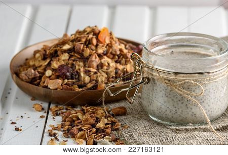 Glass Jar With Chia Pudding And A Can Of Granola On A Light Background. Copy Space