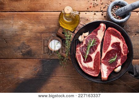 Two Fresh Raw Marble Meat, Black Angus Ribeye Steak With Spices In Iron Pan On A Old Rustic Table. R
