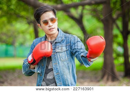 Cool Young Man Asian With Boxing Red Gloves In Park