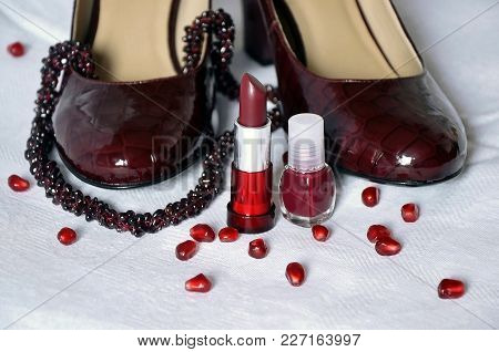 Womens Shoes, Lipstick, Nail Polish And Garnet Necklace On White Background.