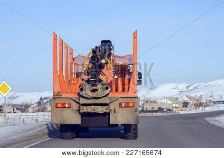 Orange Timber Transport Goes On A Country Road