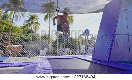 Professional Muscular Gymnast With Bare Core Jumping On The Trampoline And Doing Tricks In Air Outdo