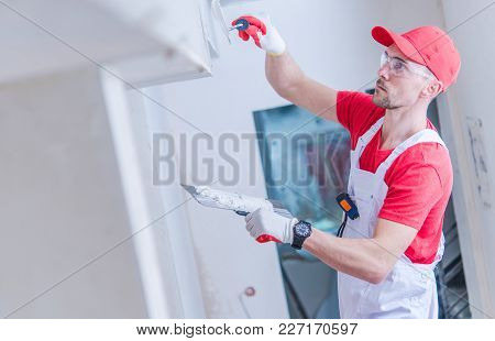 Caucasian Contractor In His 30s During Drywall Patching Work. Construction Theme.