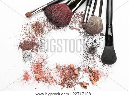 Makeup brushes with crushed cosmetic of professional artist on white background