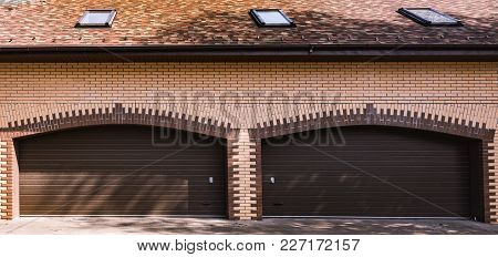 Brick Yellow Garage In A Private House With A Brown Gate Closed