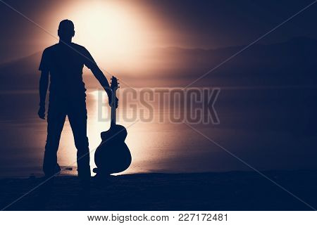 Guitarist With Acoustic Guitar Sunset Silhouette Concept Photo With Right Side Copy Space.