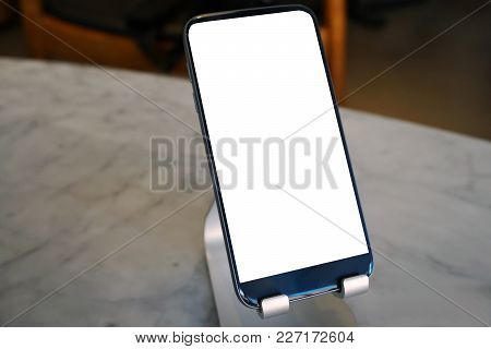 Smartphone Charged By Wireless Charger On Table In The Office.