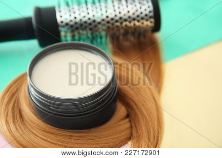 Jar with clay for styling, brush and strand of blonde hair on color background