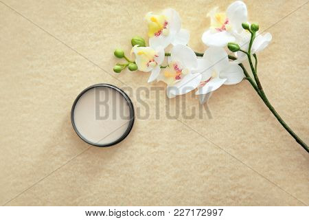 Jar with clay for hair and flowers on light background