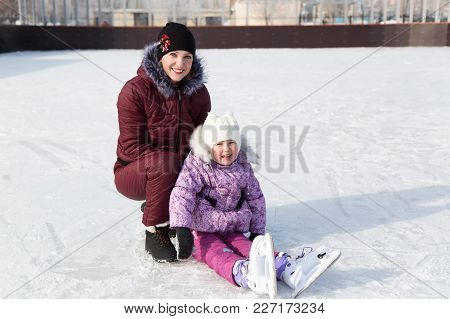 Mom Hugs Her Beautiful Daughter In The Winter On The Rink.