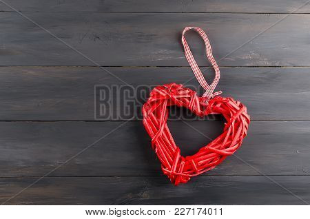 Nice Wicker Red Heart  Placed On Old Dark Wooden Table. Valentines Day Decoration On Old Background.