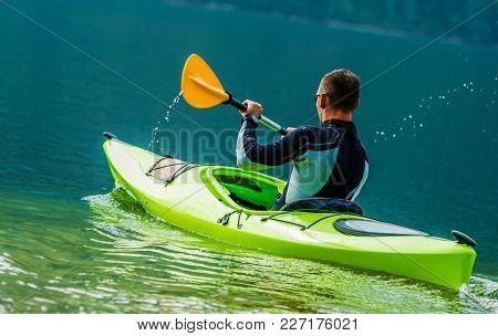 Recreational Kayak Trip. Caucasian Men In The Kayak On The Scenic Lake.
