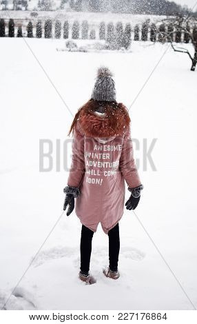 Teenage Girl Wearing Pink Coat With Slogan On Back: Awesome Winter Adventures Will Come Soon, On Whi