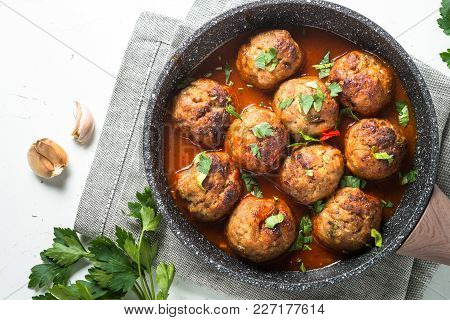 Meatballs In Tomato Sauce In A Frying Pan. Top View With Copy Space On White Background.