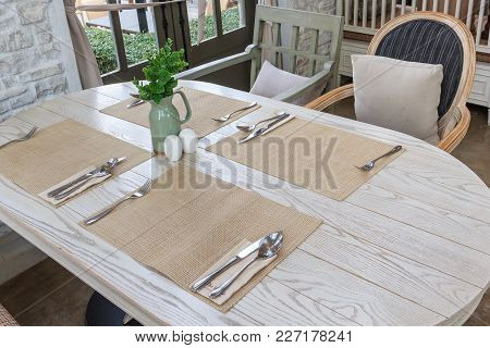 Setting The Table For Dining Room, The Table Is Decorated With Plant, Whole Scene Is Sunlight