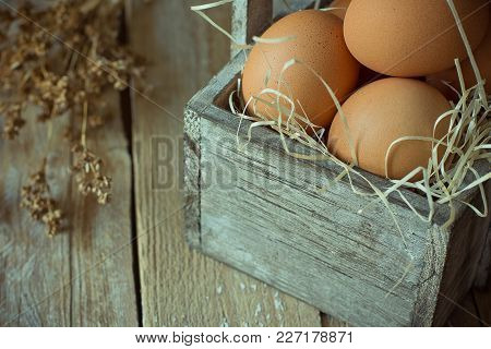Brown Organic Eggs On Straw In Vintage Wooden Box On Plank Kitchen Table. Small Bouquet Of Beige Dry