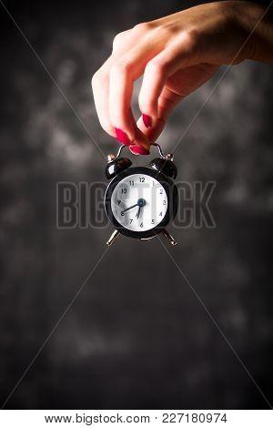 Female Hand Holding A Small Clock With Copy Space