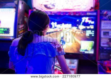 Girl Playing In The Arcade Entertainment Center Rear View