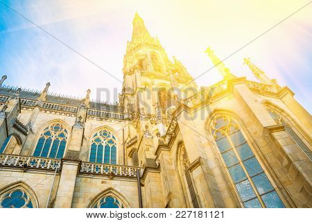 Spire Of The New Dome Gothic Cathedral In Linz Austria. Low Angle Perspective. Blue Sky Golden Sunli