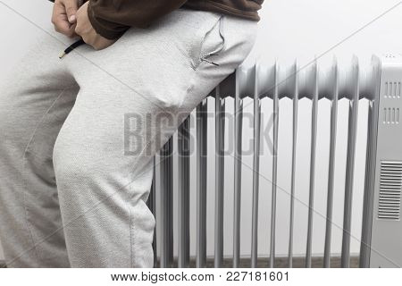 Unknown Man Sitting And Heating His Ass On Oil Heater