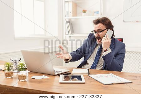 Stressed Businessman With Laptop In Modern White Office Interior, Talking On Phone And Indignantly P
